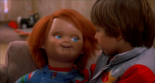 Andy and Chucky: A brown-haired 6-year-old boy looks at a doll with red hair whose wearing overalls and a striped shirt.